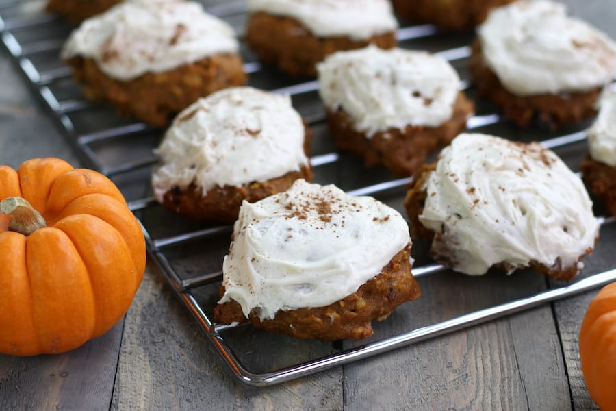 Iced Pumpkin Cake Cookies lined up on a cooling rack.