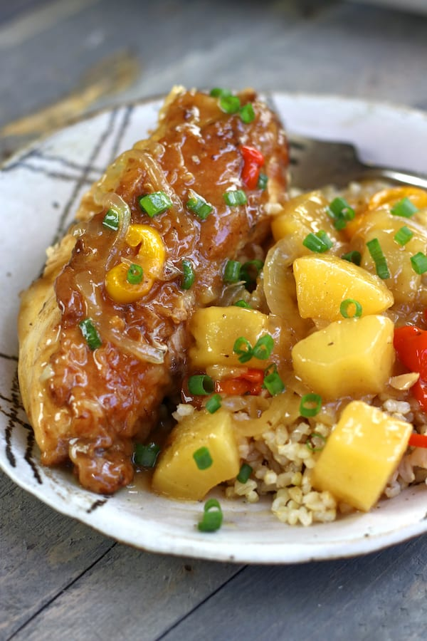 Sour and Sweet Chicken on a plate with large pineapple chunks.