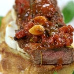 Up close Steak Pizzaiola Recipe on top of garlic toast.