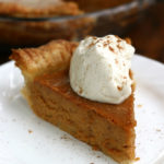 A slice of Homemade Pumpkin Pie with whipped cream.