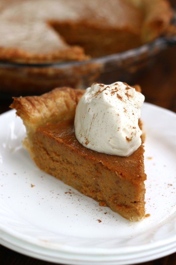 A slice of Pumpkin Pie From Scratch sitting on a white plate.