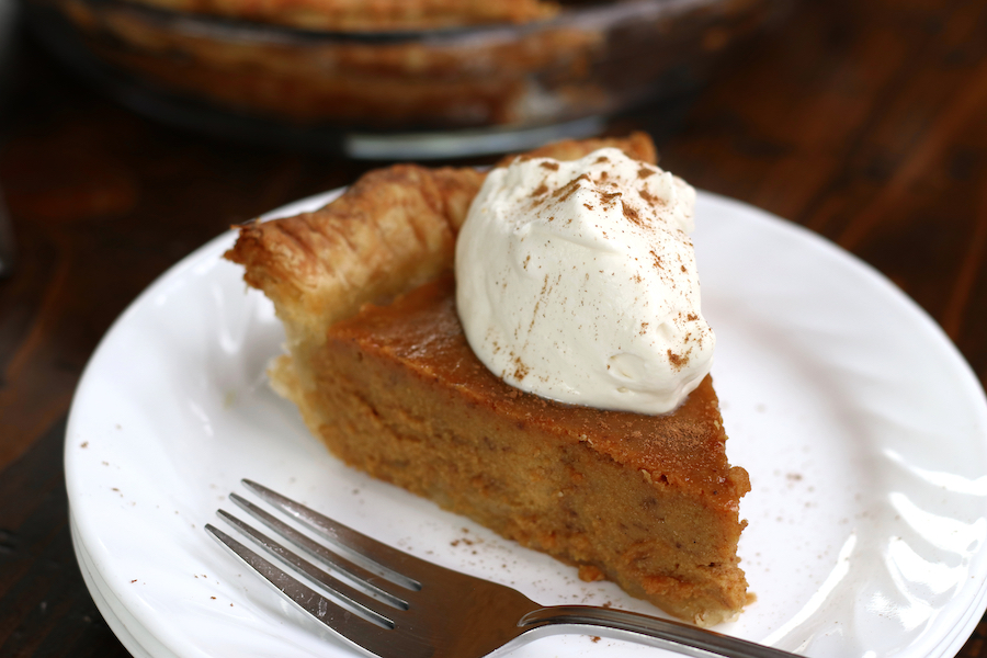 Serving of a Pumpkin Pie Recipe on a white plate with a fork.