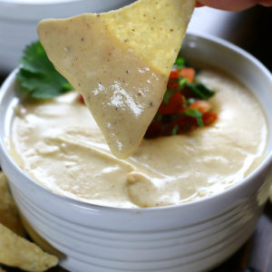 Chip dipping into Ultra Creamy Nacho Cheese.