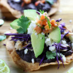 Baked Tostadas with refried black beans, shredded chicken and avocado slices.