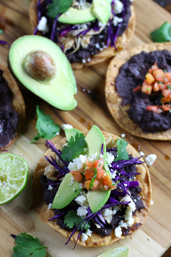 Mexican Tostadas with a cut avocado and half a lime.