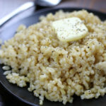 Cooked Short Grain Brown Rice on a plate with butter and pepper.