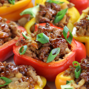 Yellow, orange and red Asian Stuffed Peppers garnished with green onions.