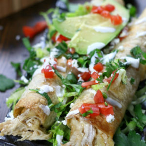 Chicken Flautas on a plate garnished with tomatoes, cilantro and avocado.