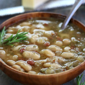 A serving of Italian White Bean Soup in a brown bowl.