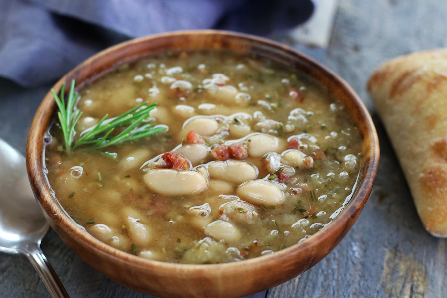 Mediterranean White Bean Soup in a brown bowl sitting on a grey table.