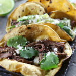 Three Shredded Beef Tacos with Cilantro Lime Coleslaw sitting on a grey plate.