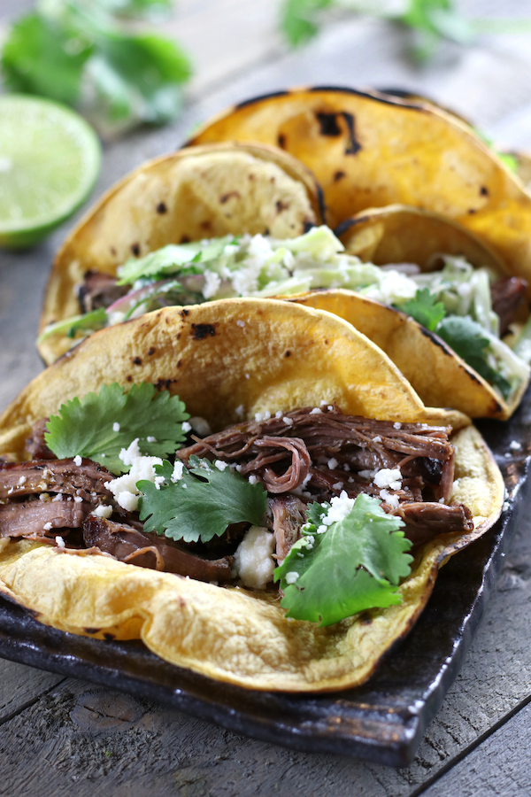 Slow Cooker Tacos garnished with Queso Fresco and fresh cilantro.