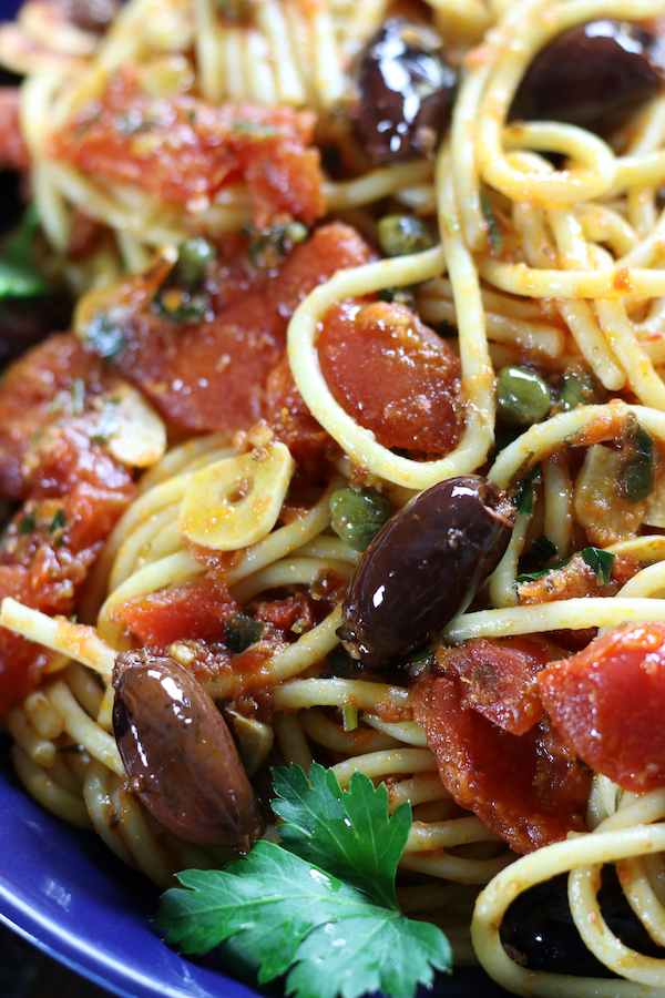 Spaghetti Puttanesca with whole olives, capers and garlic slices.