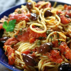 A serving of Spaghetti alla Puttanesca in a blue pasta bowl.
