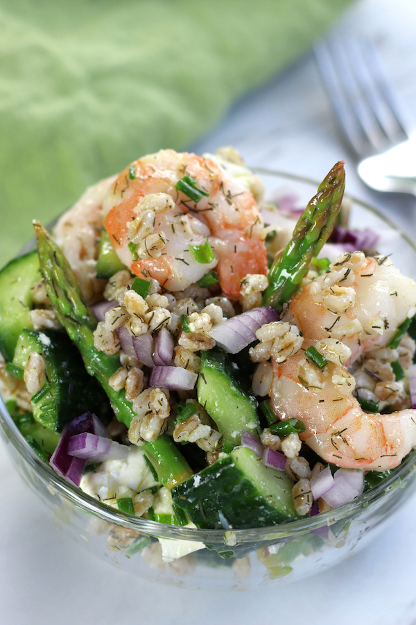 Farro Salad in a glass bowl with diced red onion, asparagus, shrimp and cucumbers.