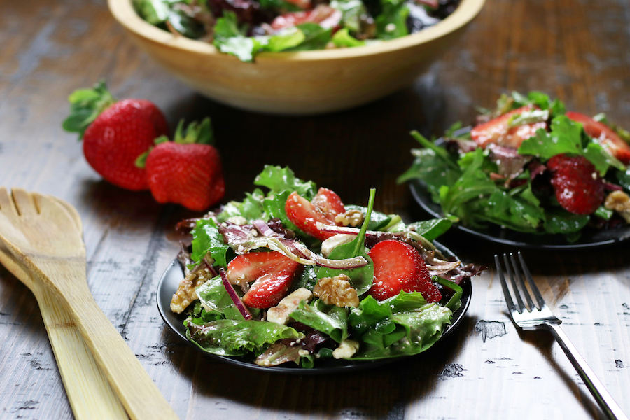 Two plates of Spring Mix Salad Recipe on a brown table.