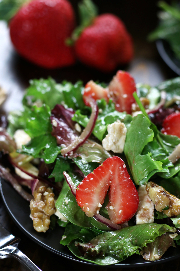 Up close photo of a plate of Spring Mix Salad with strawberries and walnuts.