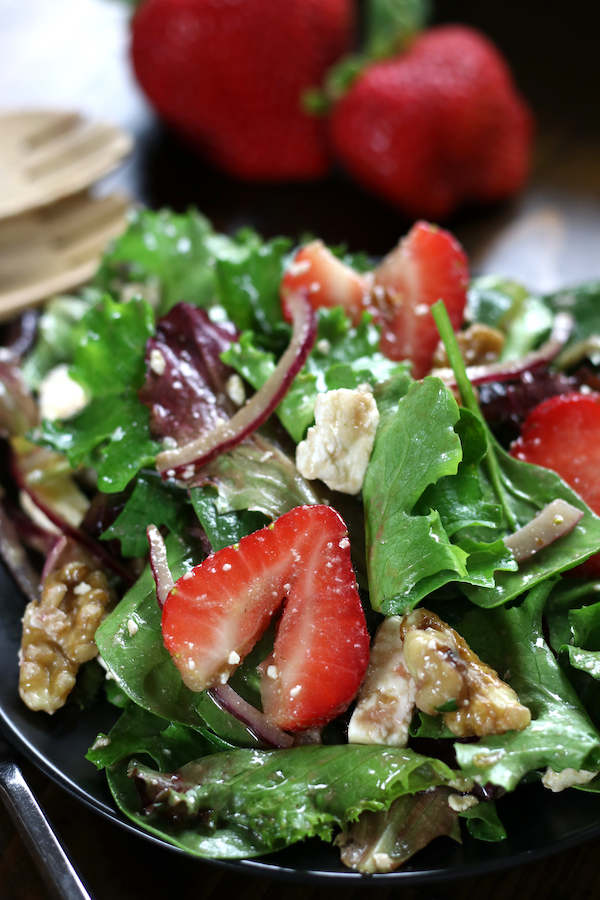 Strawberry Salad on a black plate with feta, walnuts and red onion.