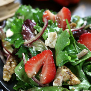 A serving of Strawberry Walnut Salad tossed in a balsamic vinaigrette.