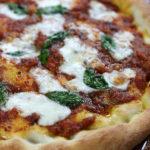 Pizza Napolentana with fresh basil leaves and mozzarella.