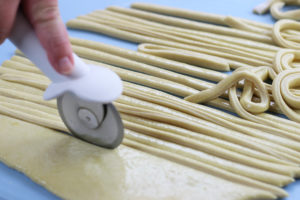 Cutting of Pici Dough into Strips using a pizza cutter.