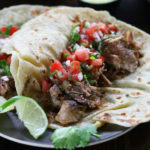 Carnitas meat in two flour tortillas with fresh salsa.