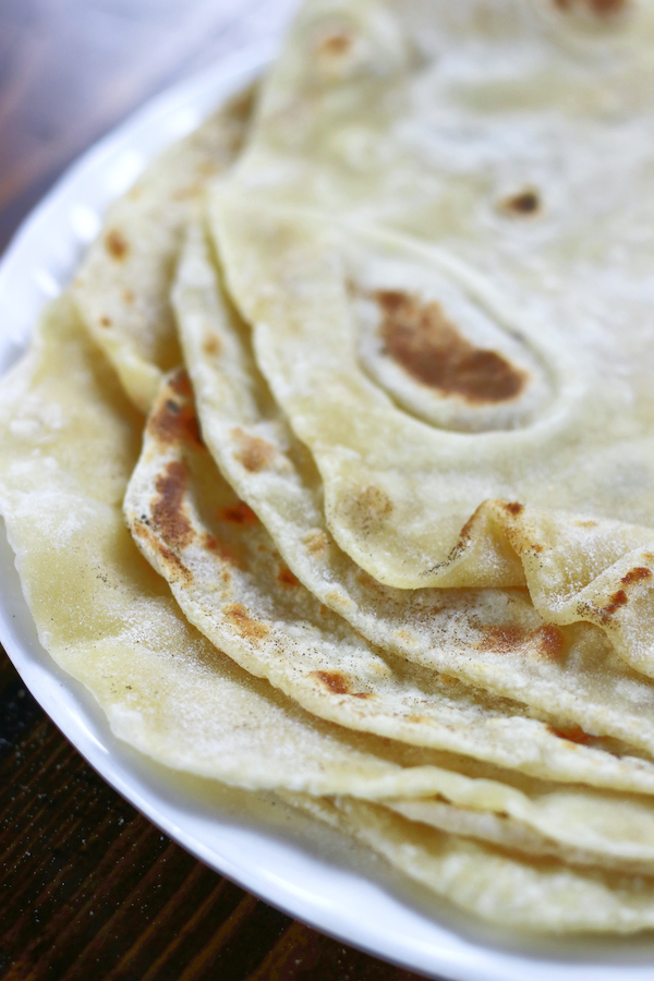 Fresh made tortillas on a white plate from Flour Tortillas Recipe.