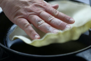 Adding Uncooked Flour Tortilla To a Heated Pan