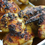 Two roasted chicken halves in a roasting pan from Citrus Chicken recipe.