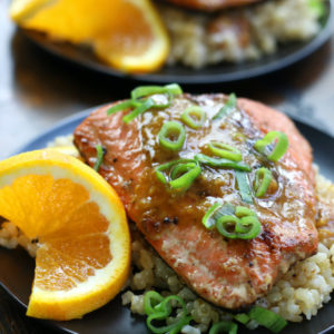 Two plates of Orange Glazed Salmon ditto on a wooden surface.