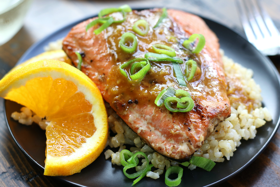 Seared Salmon with Skin on a plate with an orange slice that is curled.