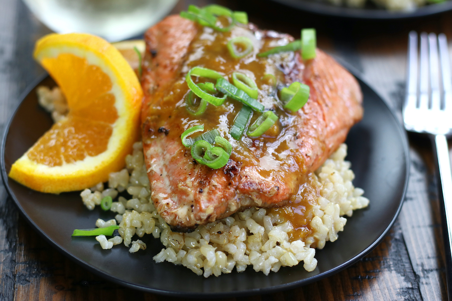 Seared and Glazed Salmon garnished with green onions and an orange slice.