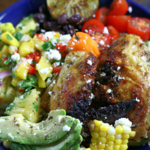 A Chicken Bowl with cut avocado, fresh cut corn, tomatoes and pineapple salsa.