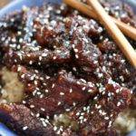 Up close photo of Crispy Sesame Beef in a blue bowl.