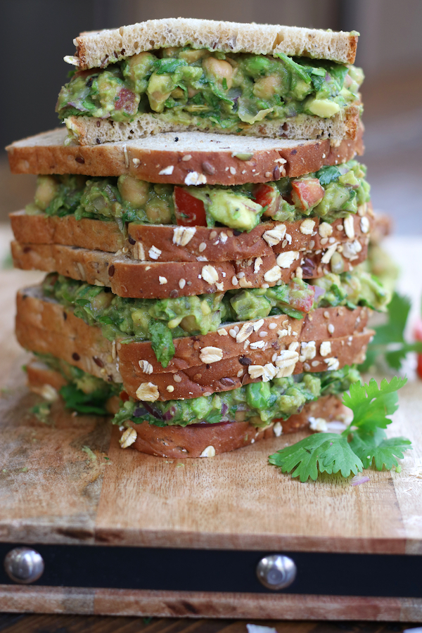 A stack of four Guacamole Sandwiches with seeded whole grain bread on a wooden cutting board.