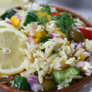 Mediterranean Risoni Salad in a wooden bowl.