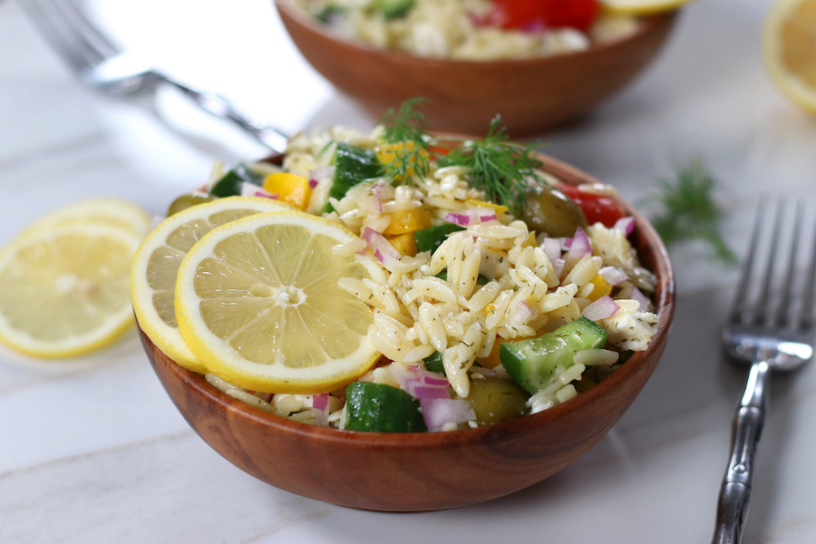 A small bowl of Orzo Pasta Salad garnished with two lemon slices and a fork sitting next to the bowl.