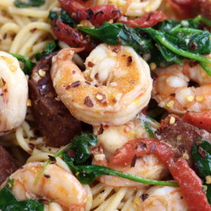 Up close photo of Prawn Spaghetti with chorizo, spinach and roasted red bell pepper strips.