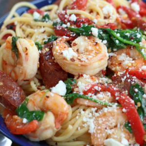 Prawn and Chorizo Pasta in a blue bowl garnished with crumbled cheese.