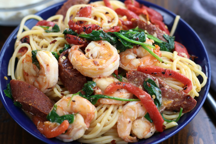 A bowl of Shrimp and Chorizo Pasta in a blue bowl sitting on a wooden table.