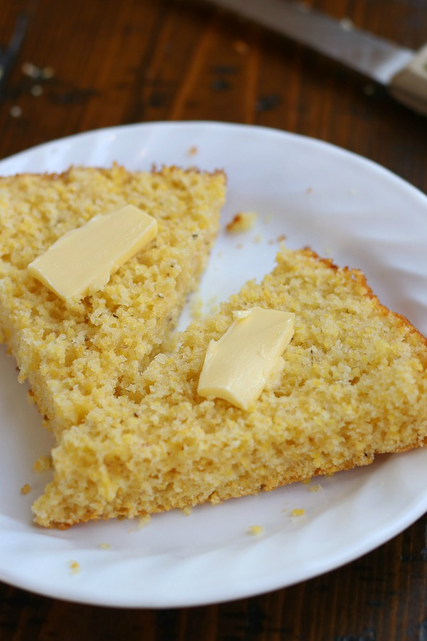 A slice of Easy Cornbread Recipe cut in half with dabs of butter.