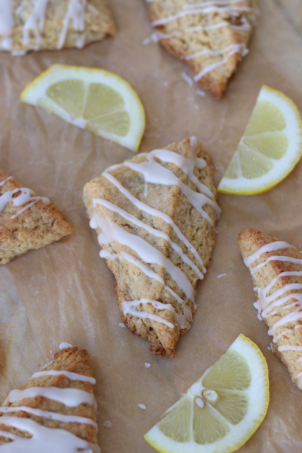 Overhead photo of Lemon Cream Biscuits on parchment with lemon slices.