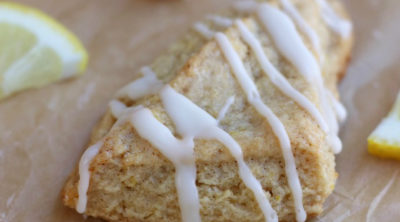 Lemon Scones sitting on brown parchment paper with a lemon glaze.