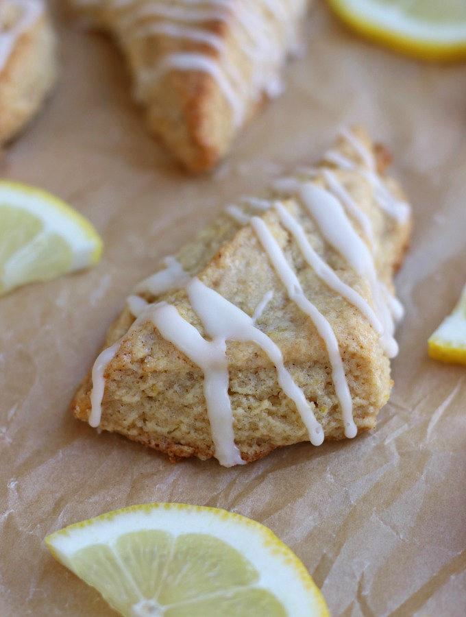Lemon Scones sitting on brown parchment paper with a lemon glaze.