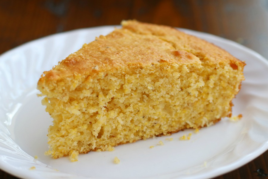 A slice of Simple Cornbread Recipe sitting on a white plate.