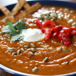 Sweet Potato Chorizo Soup garnished with roasted red peppers, cilantro and fried corn tortilla strips.
