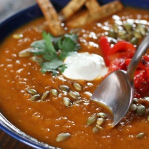 Spoon dipping into a bowl of Sweet Potato and Chorizo Soup.