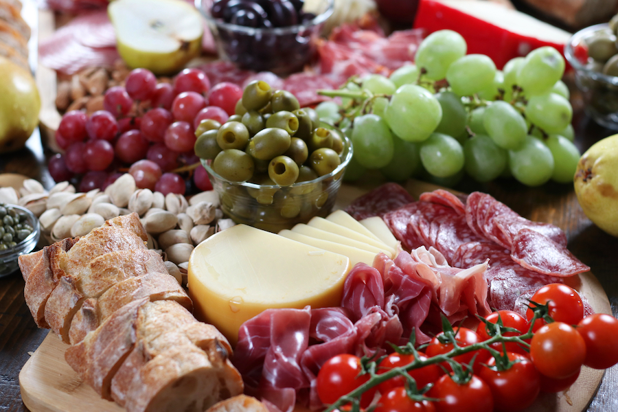 DIY Charcuterie Board with green grapes, red grapes, olives, meats, breads and cheese.