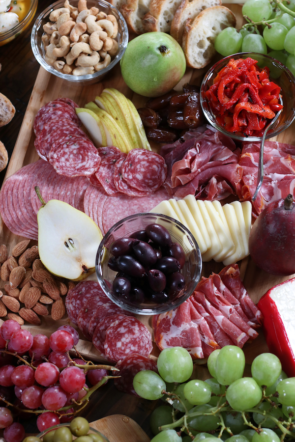 A wooden cutting board holding Italian Charcuterie Board ingredients.