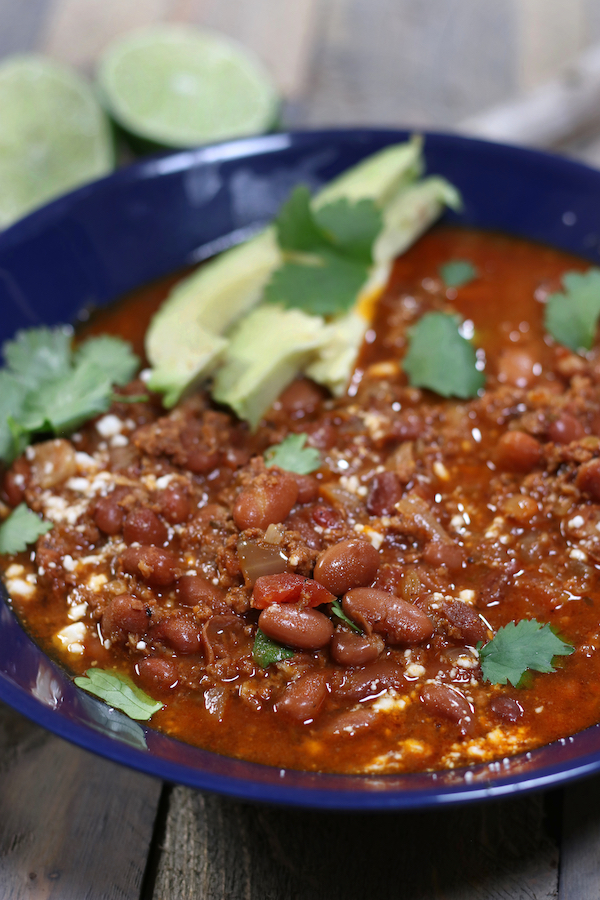 A bowl of Chorizo Beans garnished with cilantro, Mexican cheese crumbles and avocado slices.
